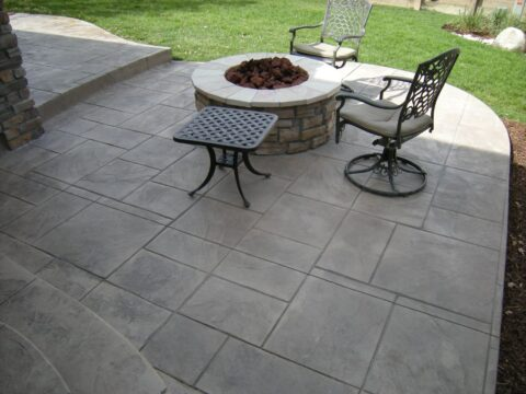 Circular stone firepit with 2 swivel chairs and a table