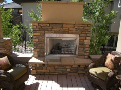 Outdoor Firepit with 2 wicker chairs with green cushions on either side