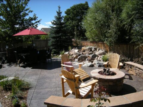 Circular stone firepit with three wooden Adirondack chairs and a table with a red umbrella in the background