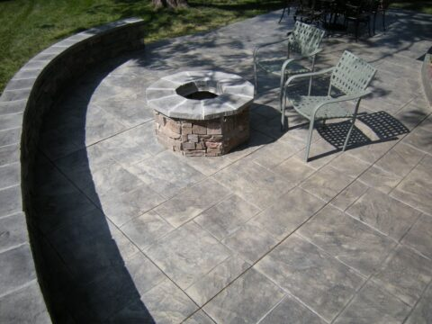 Circular stone firepit with two pale green lawn chairs in front of it on a stone patio