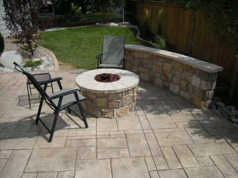 Circular stone firepit with three black and grey chairs around it