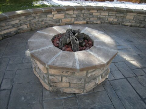 Circular stone firepit with wooden logs in the middle