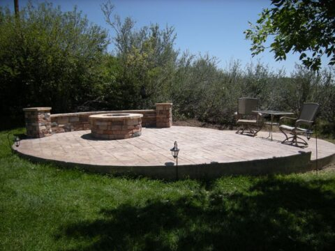 Stone firepit on a circular stone patio wtih two levels