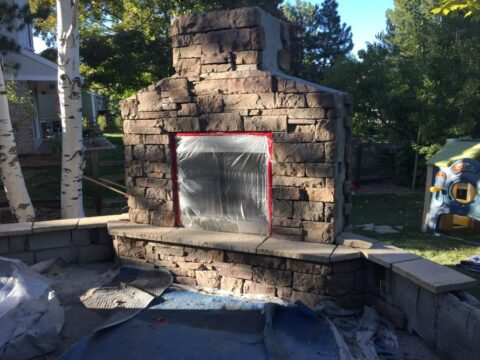 Outdoor stone fireplace with flame unfinished