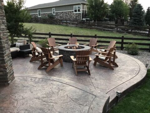 Brown wooden Adirondack chairs in a circle surrounfing a firepit