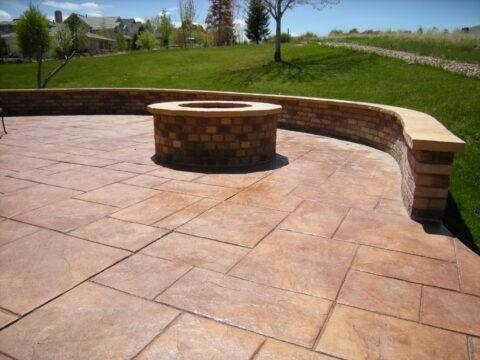 Concrete patio in rectangular pattern with firepit and wall