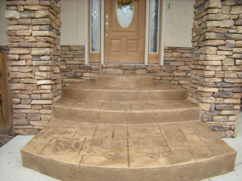concrete front entrance way steps with brown door