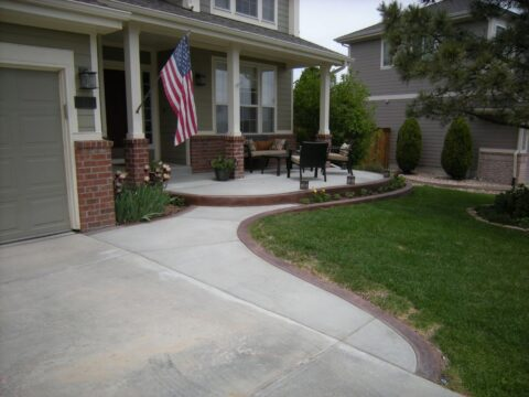 Concrete patio area with seating and driveway