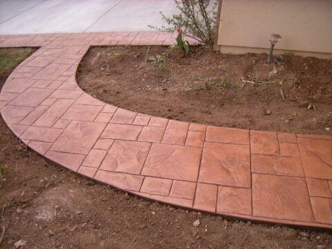 Curved concrete pathway curved with dirt on both sides