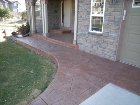 Concrete reddish pathway with curve in front of the house