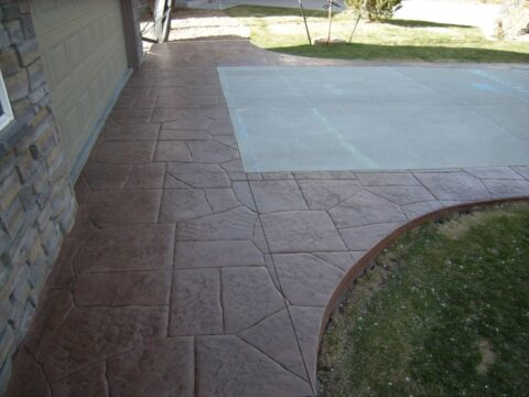 Concrete pathway and driveway two colors brown and grey with curve around lawn