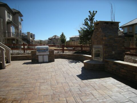 Outdoor bbq in stone kitchen with outdoor stone fireplace