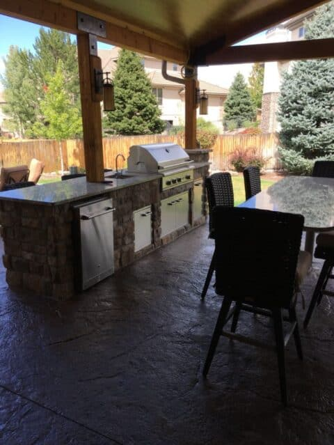Outdoor stone kitchen with bbq and table