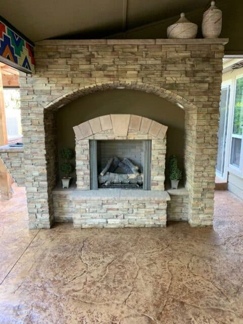 Outdoor stone fireplace with wood and archway