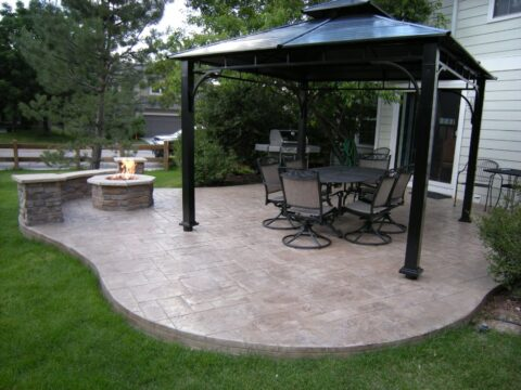Concrete patio curved with firepit and black gazebo with table and swivel chairs