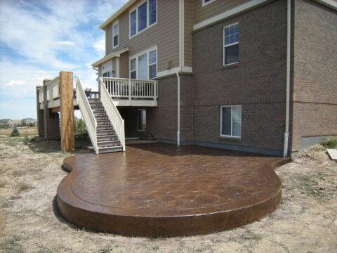 Outdoor concrete patio at bottom of stairs from deck