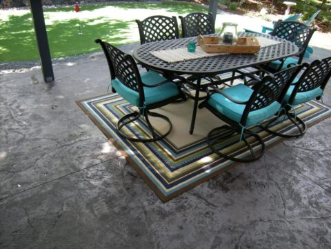 Concrete patio with table set for six with turquoise cushions and striped mat