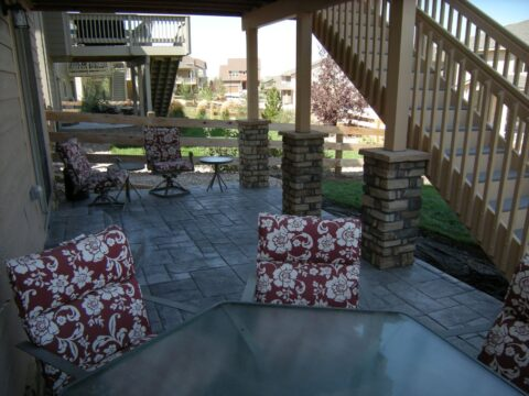 Outdoor concrete patio with table and red cushions with white flowers