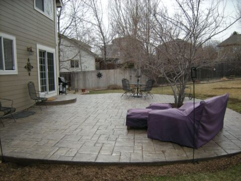 Concrete patio wtih furniture covered in purple coverings