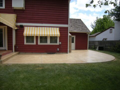 Red house with yellow and white awnings and concrete patio
