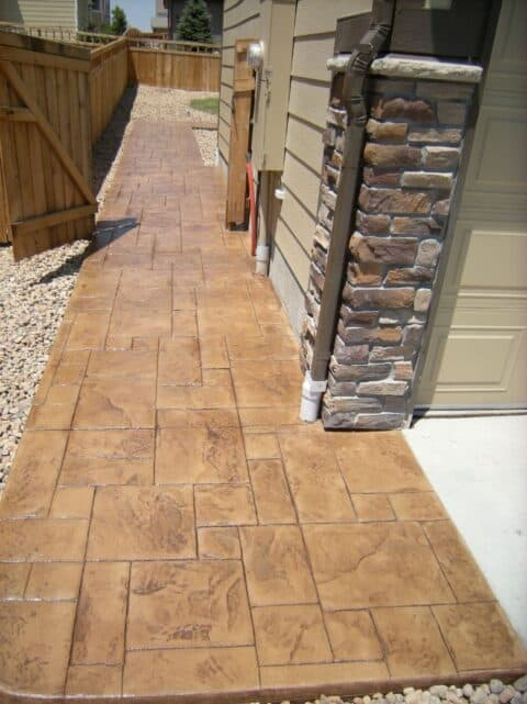 Light brown concrete walkway on side of house with stone column