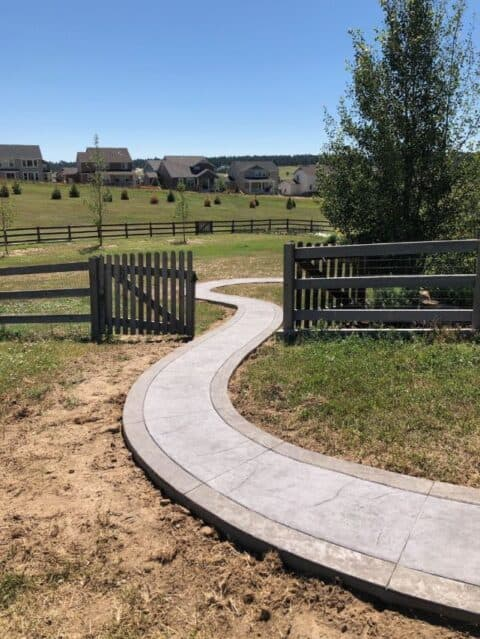 Curved concrete walkway with border going through gate