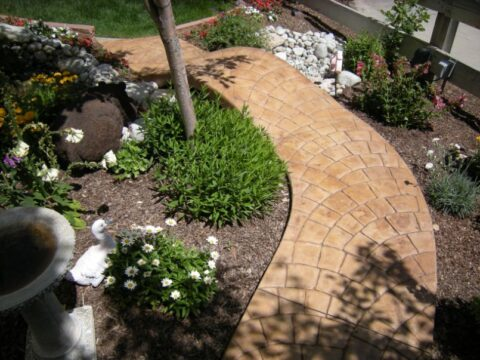 Curved beige walkway surrounded by garden