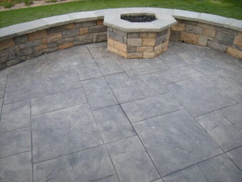 Concrete patio with firepit and wall