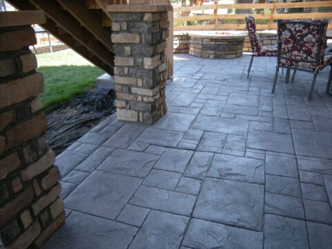 Concrete patio with rectangular pattern and pillars and firepit