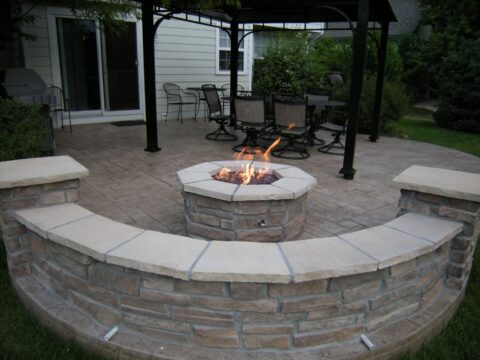 Concrete patio with curved wall and fireplace