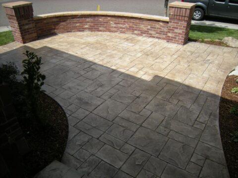 Concrete patio and brick wa;;