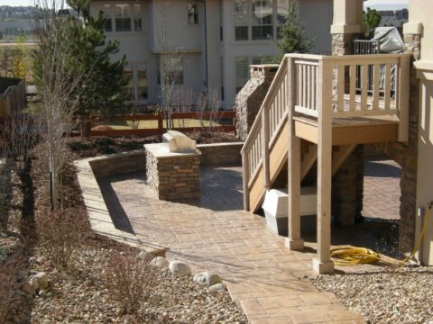 Concrete stone bbq on a outdoor patio at bottom of a staircase