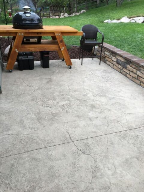 Grey concrete patio slabs with a bbq, chair and concretewall