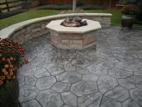 Concrete patio in stone pattern with octagon firepit and curved wall