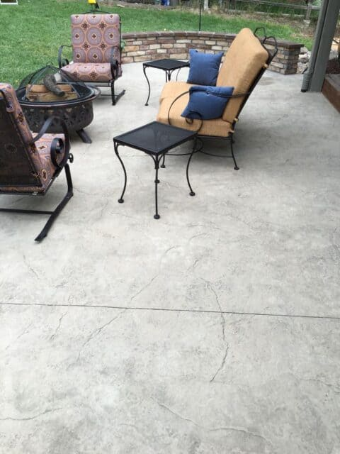 Concrete patio slabs with seating area and steel firepit with wall in background