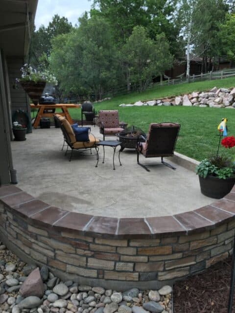 Curved wall and concrete patio with seating area and outdoor steel firepit