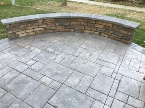 Rectangular concrete patio and stone wall
