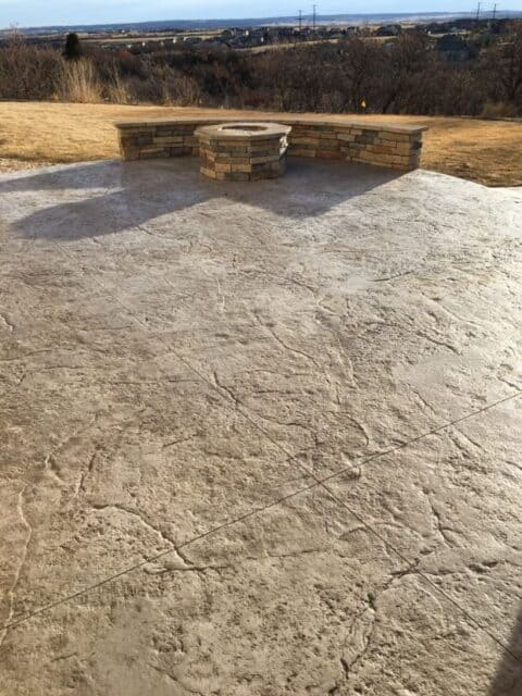 Light colored concrete patio with stone fire place and wall